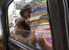 Indian kids selling pirated books to car passengers